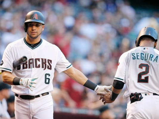 Arizona Diamondbacks' Jean Segura (2) slaps hands with David Peralta (6) after Segura scored a run against the Los Angeles Dodgers during the first inning of a baseball game Tuesday, June 14, 2016, in Phoenix. (AP Photo/Ross D. Franklin)