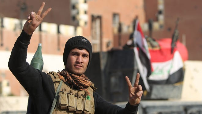 """A member of Iraq's elite counter-terrorism service flashes the """"V"""" for victory sign on December 28, 2015 after Iraqi forces recaptured the city of Ramadi, the capital of Iraq's Anbar province, about 110 kilometers west of Baghdad, from the Islamic State (IS) jihadist group. Iraq declared the city of Ramadi liberated from the Islamic State group and raised the national flag over its government complex after clinching a landmark victory against the jihadists."""