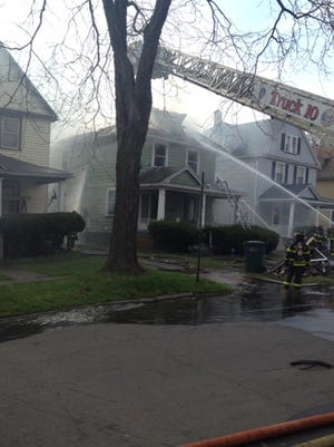 Firefighters at the scene of a house fire on Post Avenue on Saturday morning.