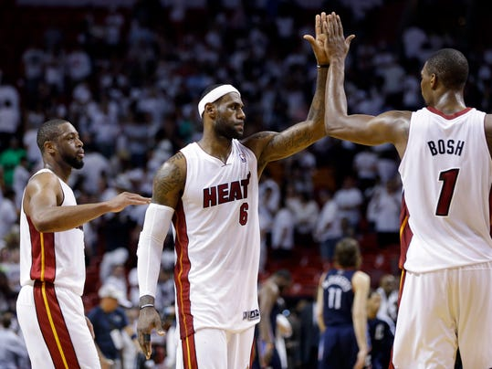 Miami Heat's LeBron James (6) high-fives Chris Bosh (1) after the Heat defeated the Charlotte Bobcats 101-97 in Game 2 of an opening-round NBA basketball playoff series, Wednesday, April 23, 2014, in Miami. At left is Dwyane Wade. (AP Photo/Lynne Sladky)