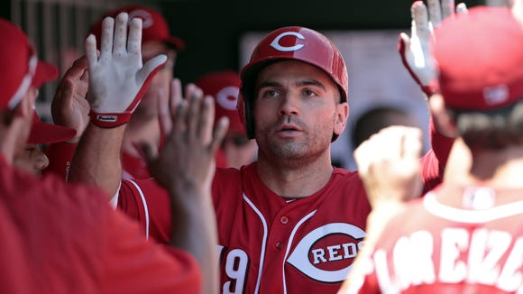 Reds first baseman Joey Votto is high-fived in the