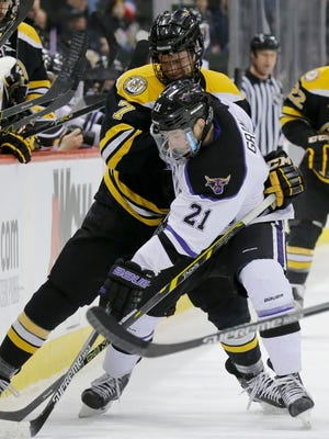Michigan Tech forward Reid Sturos (7) and Minnesota State's Chase Grant (21) battle for the puck during last week's WCHA title game. Sturos is one of three Brighton natives on a Tech team that makes its first NCAA tournament appearance in 34 years today.
