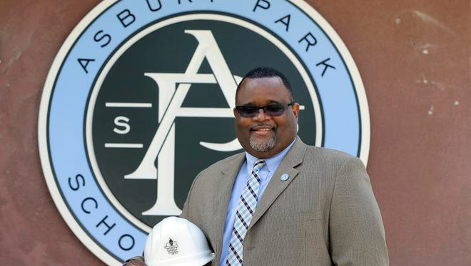 """Dr. Lamont Repollet, superintendent of Asbury Park School District, talks about his vision for the 2016-2017 school year with members of his staff at the Asbury Park Board of Education building in Asbury Park, NJ Thursday August 25, 2016.  The hard hat is a symbol of my vision of """"Building A Brighter Future."""""""