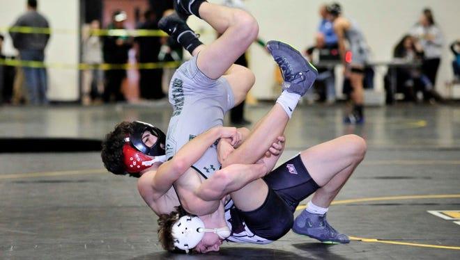 Clifton's Matthew DePasque flips DePaul's Connor O'Neil during the Passaic County finals.