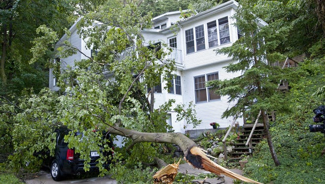 Storm damage on Lovers Lane in Grand Haven on Friday, July 7, 2017. Nearby, a 72-year-old man was reportedly killed overnight when a large tree fell on his home during a severe thunderstorm on Poplar Ridge. (Cory Morse /The Grand Rapids Press via AP)