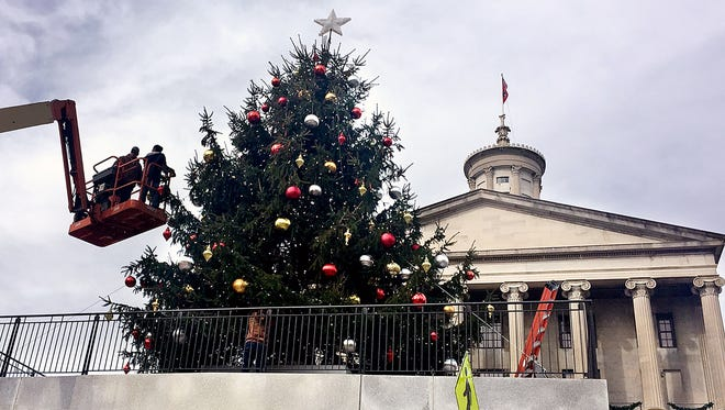 Workers decorate the state Christmas tree Tuesday at Legislative Plaza. The tree-lighting will be at 5:30 p.m. Monday.