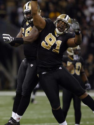 Anthony Hargrove (69) and Will Smith (91) celebrate after a play against the Falcons Monday night at the Superdome in New Orleans.
