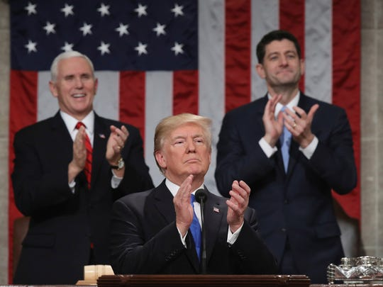 President Donald Trump pauses as he gives his first State of the Union address in the House chamber of the U.S. Capitol to a joint session of Congress in January 2018 in Washington as Vice President Mike Pence and then-House Speaker Paul Ryan applaud.