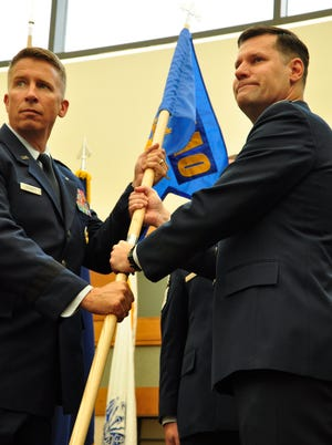 Brig. Gen. Patrick Doherty, director of services, headquarters Air Force, receives the guidon from outgoing AFMAO commander Col. John Devillier during Friday's change of command ceremony at Dover Air Force Base.