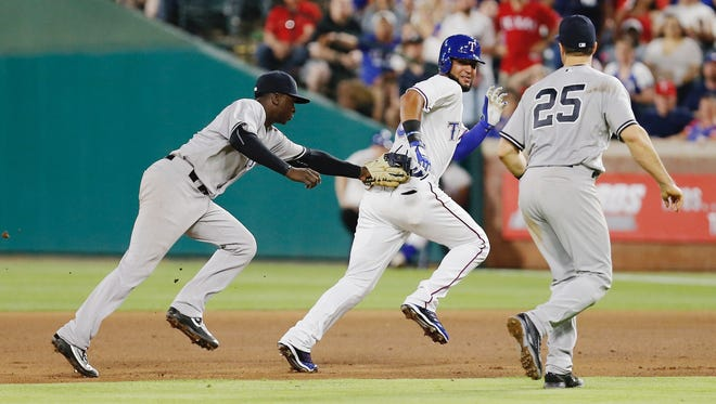 Mark Teixeira (25) looks on as Yankees shortstop Didi Gregorius, left, tags out Texas Rangers Nomar Mazara on a run down during the seventh inning. Mazara reached base on a single to left field that ended Yankees starter Nathan Eovaldi's bid for a no-hitter.