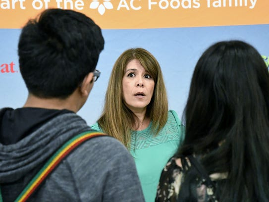 An exhibitor speaks with students at the third annual