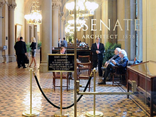 Lobbyists wait outside the Senate Chamber as legislative members work on the state budget at the state Capitol on Friday, March 31, 2017, in Albany, N.Y.