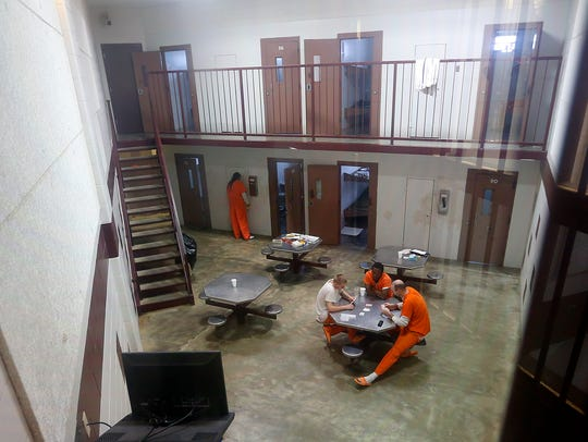 Inmates play cards inside a pod at the Miller County