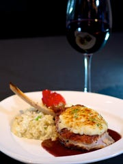When visiting Cuizine Restaurant and Lounge in Satellite Beach, a must-try dish is the Cast Iron 14-ounce Parmesan Crusted Veal Chop with oyster scallion risotto.