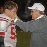 Sheridan head coach Paul Culver Jr. consoles senior Brandon Sigler following an overtime loss in 2010. Culver resigned after 44 years of coaching following his team's triple-overtime win against New Lexington on Friday.