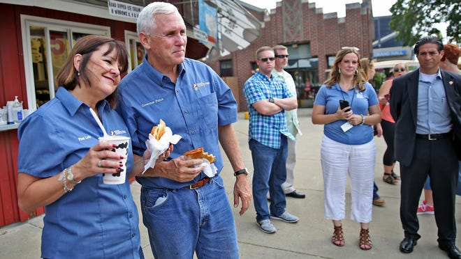 Gov. Mike Pence and First Lady Karen Pence pose for photos at the Dairy Barn on opening day of the Indiana State Fair on Aug. 5.