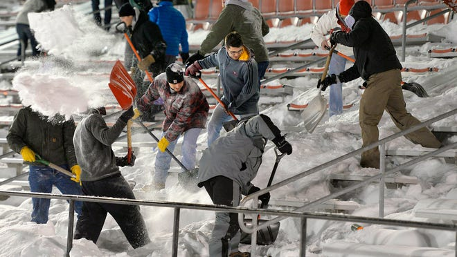St. John's University football fans, players and even monks joined in Monday night to clear Clemens Stadium of snow for the upcoming MIAC playoff football game against St. Scholastica.
