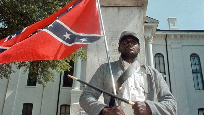 In this May 8, 2000, file photograph, Anthony Hervey holds a Confederate flag while standing underneath the Confederate monument in Oxford, Miss. The Highway Patrol says 49-year-old Hervey was killed Sunday, July 19, 2015, when his 2005 Ford Explorer left the roadway and overturned on Mississippi Highway 6 in Lafayette County. Hervey, of Oxford, has drawn attention over the years for opposing efforts to change the flag. He said he dressed in Rebel soldier garb to honor blacks who served with the Confederacy during the Civil War.
