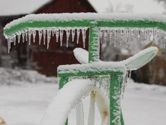 Icicles form on an old bicycle outside the Farmer's Tavern in Mulliken on December 23, 2013.