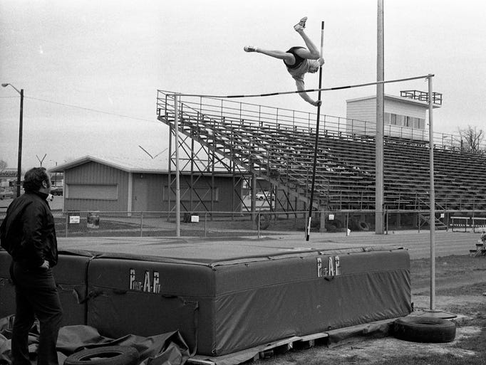 With Jeff track coach Bob Downing, left, looking on, pole vaulter Bob Keller, a sophomore, gets in a practice jump and heads for a soft landing on Jeff's new Port-A-Pit, a recent equipment gift from members of the Golden Broncho Club. The group, formed about a year ago by a sports-minded band of local businessmen, is providing additional athletic equipment for the Lafayette junior high schools as well as Jeff in an effort to east the strain on the school's athletic budget. Photo taken April 14, 1974.