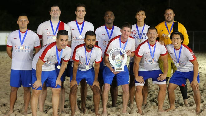 Quality Distributors pose for a team photo with the champions trophy of the 2017 LandShark Beach Soccer League and gold medals following the team's 5-2 win over the Bank of Guam Strykers, ousting the team in the league's double-elimination playoffs at the Guam Football Association National Training Center beach soccer court July 15, 2017. In the front row, from left to right, are RC Salas, Paul Long, Joseph Preseault (holding trophy), Caleb Barretto, and Jared Pangindian. In the back row, from left to right, are Diego Cardona, James Bush, Kyle Legozzie, Barinedum Bakor, James Lee, and Brett Maluwelmeng.
