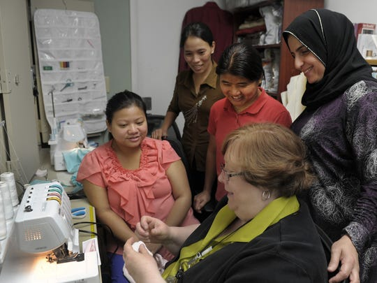 Rita Atkins teaches sewing skills to a group of refugees