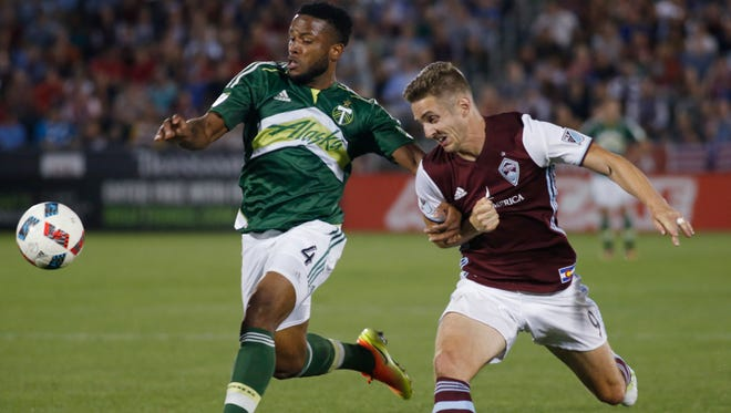 Portland Timbers defender Jermaine Taylor, left, kicks the ball away from Colorado Rapids forward Kevin Doyle during a foot race to gain control of the ball in the second half of an MLS soccer match Monday, July 4, 2016, in Commerce City, Colo. The teams played to a 0-0 tie. (AP Photo/David Zalubowski)