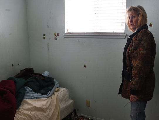 Landlord Jeanette McDaniel surveys the condition of