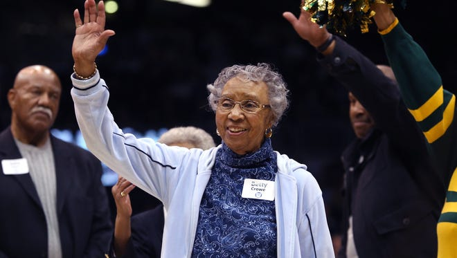 Betty Crowe, widow of Ray Crowe, the coach of the 1955-56 Crispus Attucks High School teams that won the Indiana state high school basketball championships, is introduced during a 60th anniversary tribute to the teams during a time out at the Butler-Marquette game at Hinkle Fieldhouse in Indianapolis on Wednesday, Feb. 25, 2015.