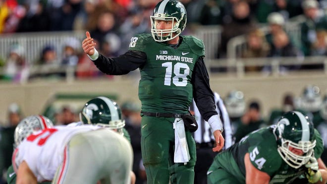 Michigan State quarterback Connor Cook gestures to a teammate during last season's loss to the Buckeyes at Spartan Stadium. Cook threw for 358 yards and two touchdowns, but the Spartans lost, 49-37.