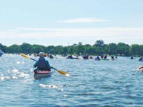 A line of 75 canoes, kayaks and standup boards takes
