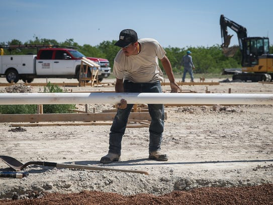Lone Star Contracting apprentice Moses Ramirez places a pipe in the trench May 10 at the Journey Recovery Center construction site.