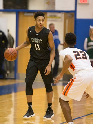 Trinity Shamrocks guard David Johnson (13) brings the ball up the court during the championship game of the Louisville Invitational Tournament between the Fern Creek Tigers and the Trinity Shamrocks.