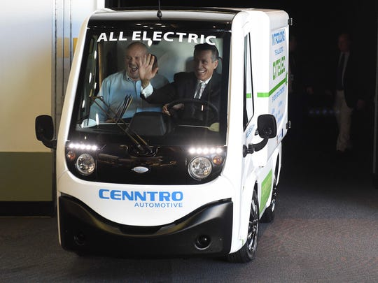 Gov. Brian Sandoval, right, and Sparks Mayor Geno Martini arrive at a news conference in a Cenntro electric vehicle.