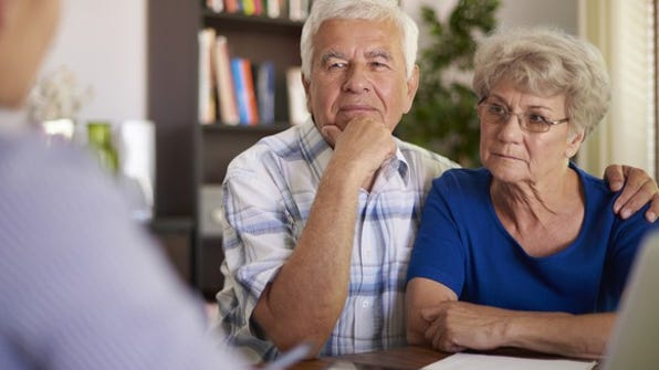 Serious senior couple listening to a financial advisor