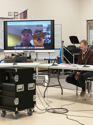 Pictured are Activities Director Greg Garmen via computer at the School Board meeting with Superintendent Jeremy Olson listening in from the high school's choir/orchestra room.