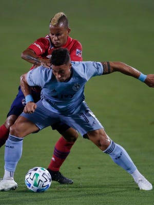 Sporting KC's Erik Hurtado, front, shields the ball from FC Dallas' Michael Barriosduring the first half of an MLS soccer game in Frisco, Texas, Wednesday, Oct. 14, 2020.