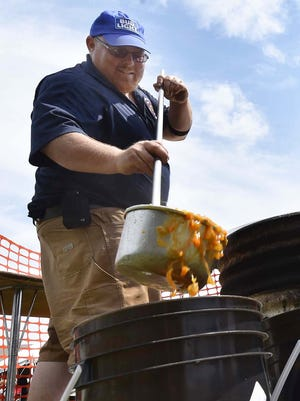 Matt Phillips ladles booyah from large steel kettles into small containers during last year's Belgian Days in Brussels. Volunteers made 150 gallons of booyah for the festival.
