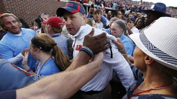 Mississippi football coach Hugh Freeze is congratulated by fans as he walks off the field after their 23-17 win over No. 3 Alabama, 23-17 in an NCAA college football game in Oxford, Miss., Saturday, Oct. 4, 2014. (AP Photo/Rogelio V. Solis)