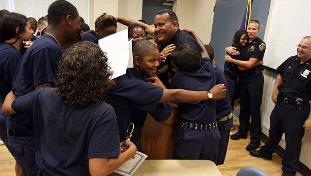 Graduates hug Police Officer David Zenon after the 12th annual graduation ceremony of the Town of Greenburgh Police Department's Summer Youth Camp in 2010 at Anthony F. Veteran Park in Ardsley.