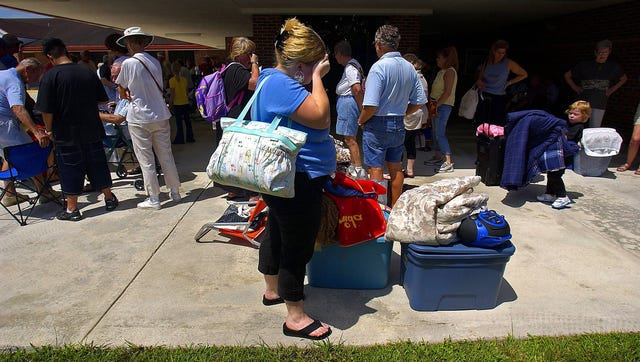 Tiffany Lenoir of Stuart stands in a line of people waiting to get into a shelter at Pinewood Elementary School in Stuart on Sept. 3, 2004 as Hurricane Frances headed toward the Treasure Coast.