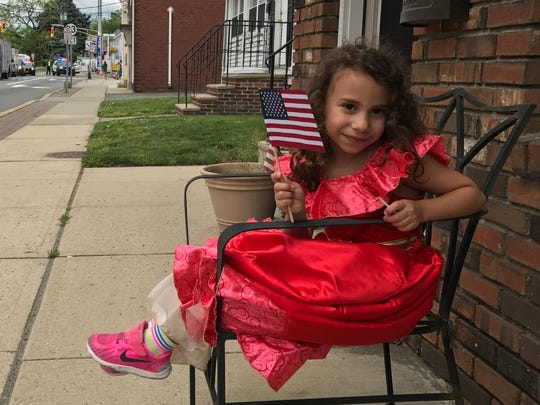 Stella Saggio, 5, of Little Falls, hangs out on the Memorial Day parade route on Saturday, May 27, 2017 on Main Street.