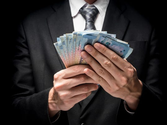 Close up of man in black suit holding a lot of cash on black background