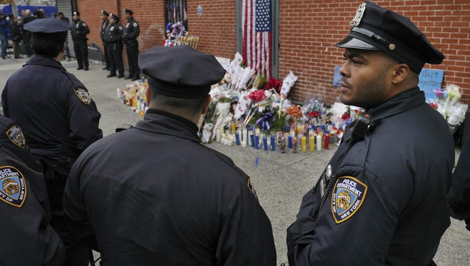 Police officers pay their respects Monday at a makeshift memorial near the site where two police officers were murdered Saturday in Brooklyn.