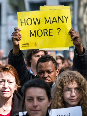 A protestor holds up a sign during a demonstration outside of an emergency EU summit in Brussels on Thursday, April 23, 2015. Protestors on Thursday called on EU leaders to take more effective action to save lives in the Mediterranean, where hundreds of migrants are missing and feared drowned in recent days. (AP Photo/Geert Vanden Wijngaert)