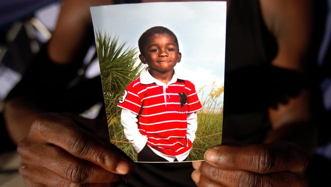 A picture of Andrew Faust Jr., 5, who was killed by gunfire in Fort Myers is held by his mother.
