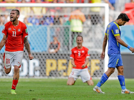 Ecuador's Cristhian Noboa, right, leaves the pitch as Switzerland's Valon Behrami, left, and Stephan Lichtsteiner celebrate after the group E World Cup soccer match between Switzerland and Ecuador at the Estadio Nacional in Brasilia, Brazil, Sunday, June 15, 2014. Switzerland won the match 2-1. (AP Photo/Michael Sohn)