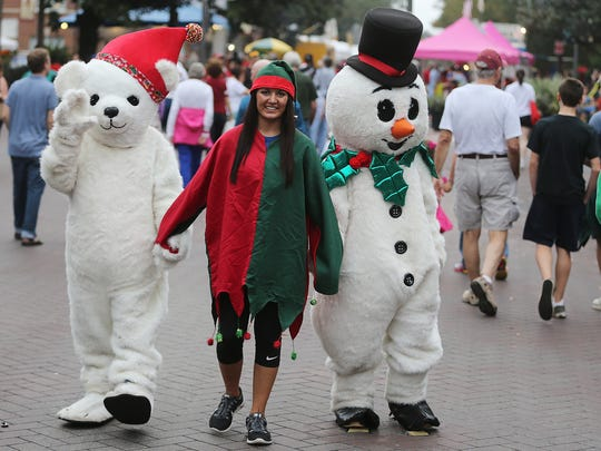 A Winter Festival attendee holds hands with a Christmas