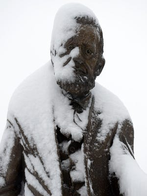 The statue of Thomas M. Cooley, the namesake of Cooley Law School, is covered with snow in downtown Lansing Thursday, Feb. 25, 2016 as cleanup continues from the snowstorm that swept through the area on Wednesday. Almost 10 inches of snow fell on the Lansing area Wednesday, with some areas of Eaton and Clinton counties getting as much as 12. Another two inches is expected to fall today.