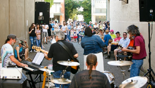 A crowd gathers to listen to Ayanarr perform outside of Taproot at Make Music Day in Downtown Salem on Wednesday, June 21, 2017. Make Music Day is a global celebration of making music that takes place every year on June 21.